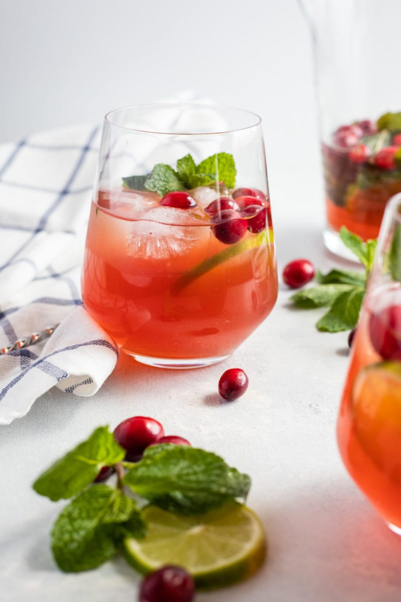 The mojito cocktail in a glass next to fresh cranberries.