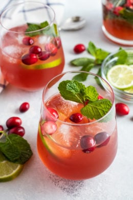 A cranberry mojito served in a glass with a sprig of mint.