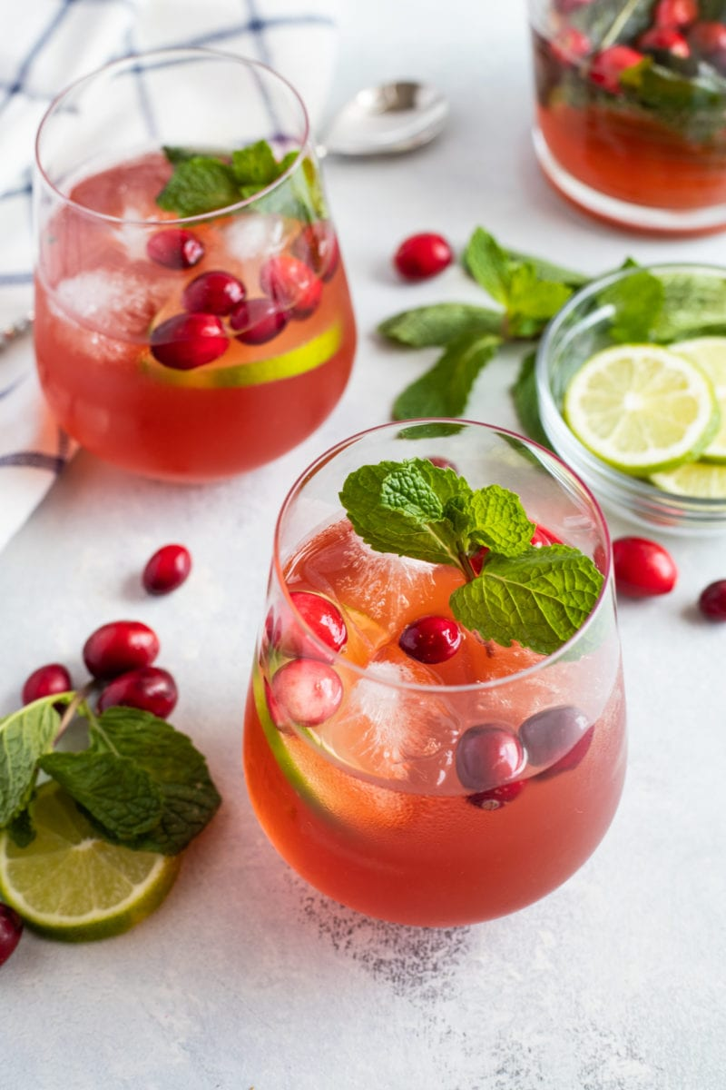 Two cocktails next to fresh cranberries, mint and lime slices.