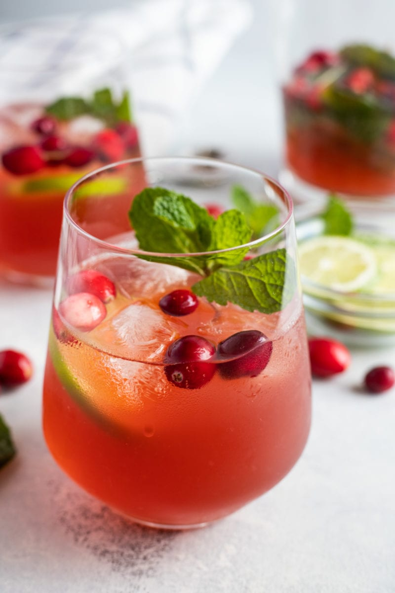 Close up of a cranberry mojito served in a glass with ice.