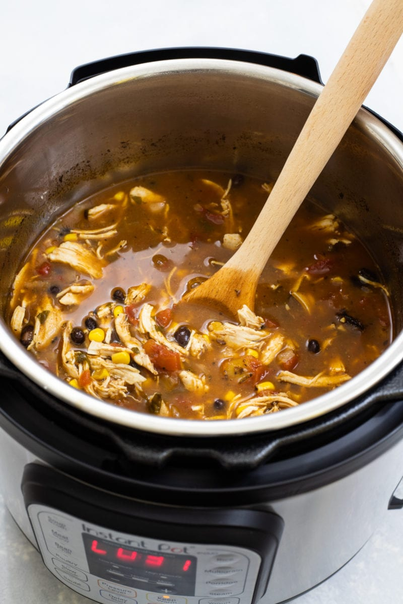 The soup in an Instant Pot with a wooden spoon.