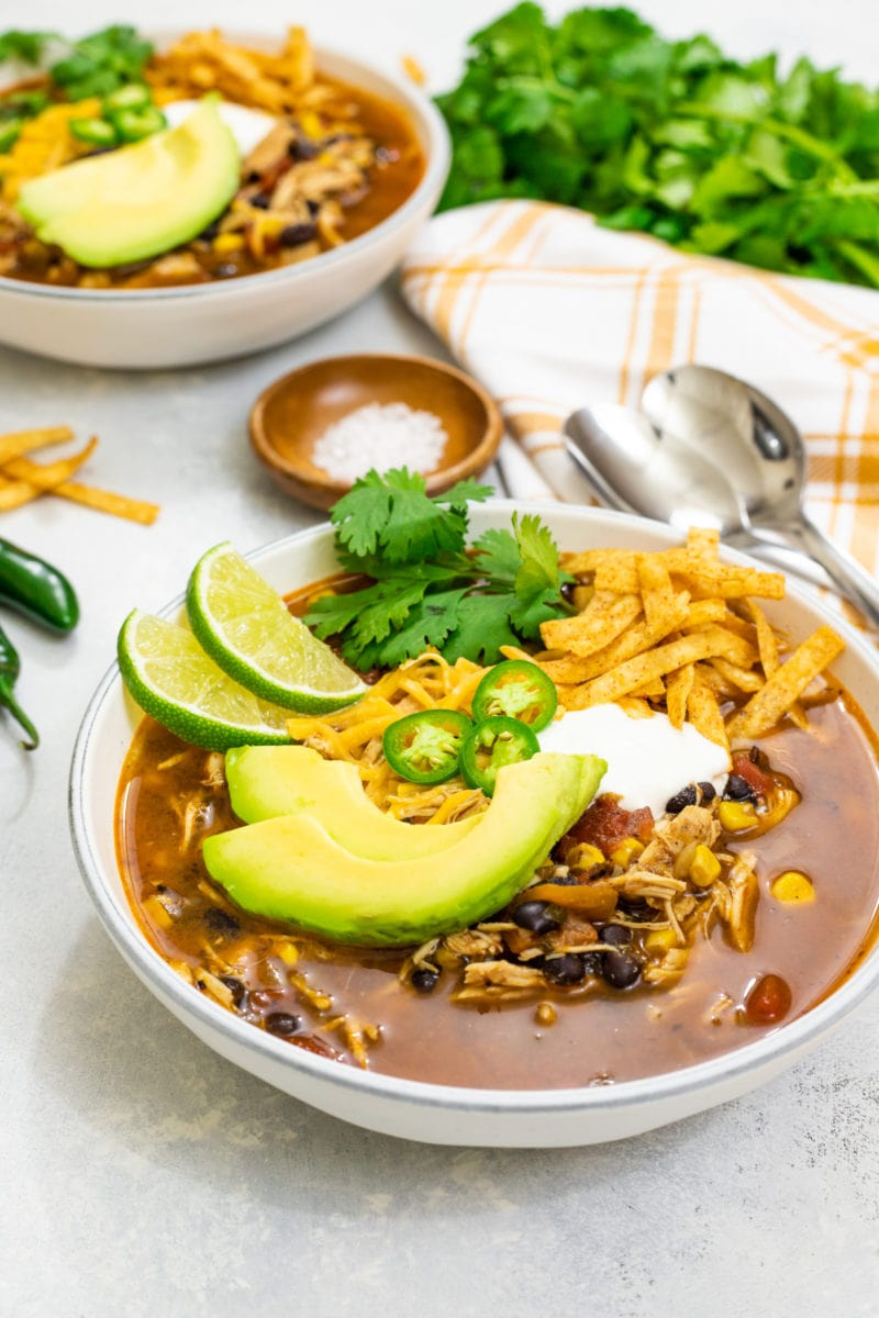 Chicken tortilla soup served in a bowl with sour cream, sliced avocado, cilantro and sliced jalapeno.