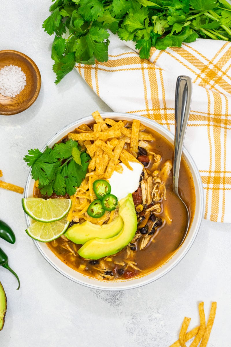 Instant Pot chicken tortilla soup topped with sour cream, tortilla chips and lime wedges.