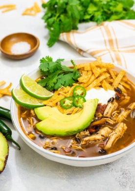 easy Instant Pot Chicken Tortilla Soup is filled with spicy flavors, shredded chicken, black beans, fire roasted tomatoes, and corn.