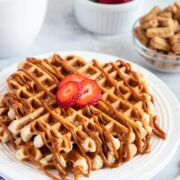 Two waffles stacked on top of each other and topped with fresh sliced strawberries.