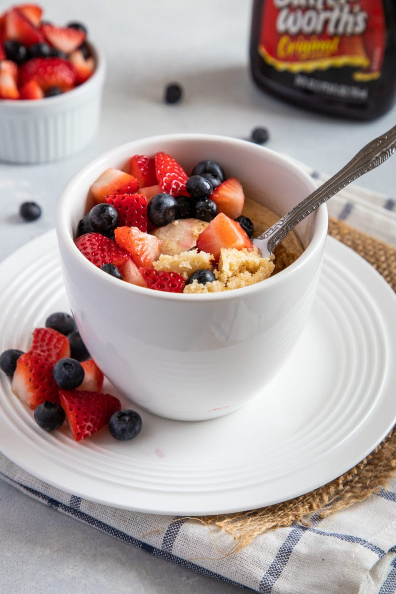Pancake with fresh berries served in a mug with a spoon.
