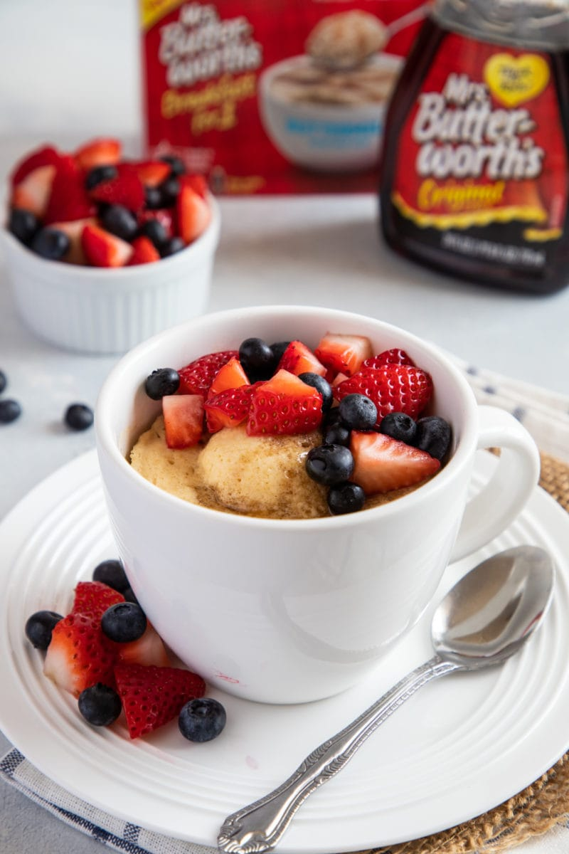 Close up of a mug with pancake and fresh berries.