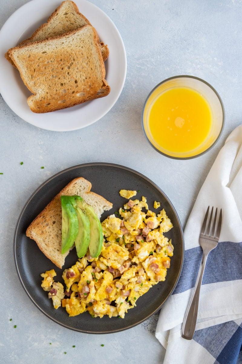 huevos revueltos con jamon y queso servidos con pan tostado y aguacate