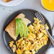 Ham and cheese egg scramble on a plate with toast and sliced avocado.