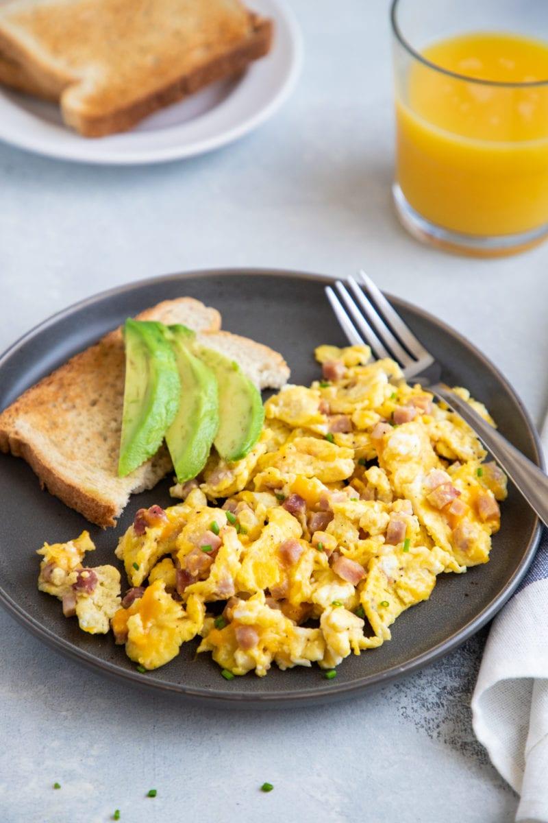 huevos revueltos con jamon y queso servido con pan tostado y aguacate