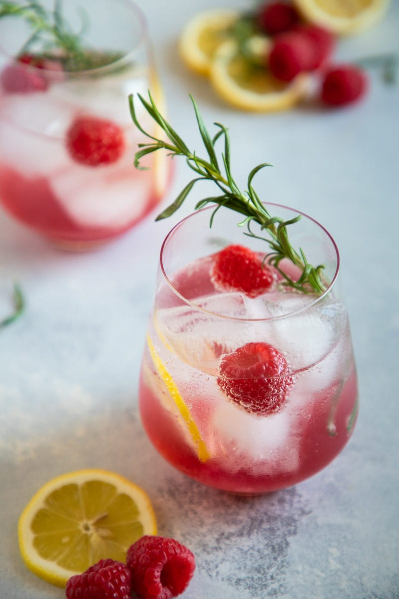 raspberry lemon wine spritzer served in a glass with lemon slices, raspberries and rosemary for garnish