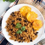 Black beans and rice on a plate garnished with fresh cilantro.
