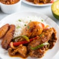 Dominican Braised Chicken or Pollo Guisado served on a plate with white rice, beans and maduros