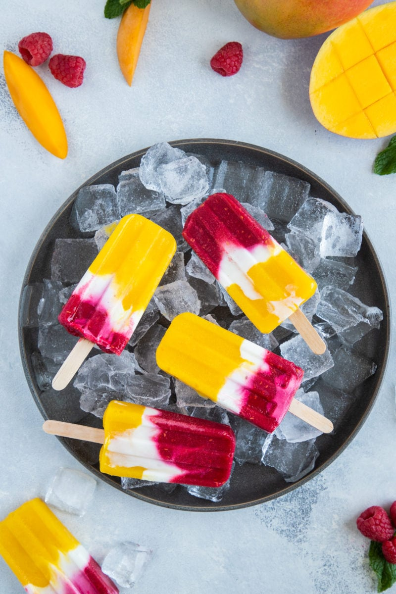 Mango Raspberry Yogurt Popsicles set on a gray plate over ice.