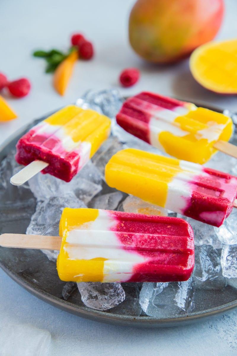 Mango Raspberry Yogurt Popsicles set on a gray plate over ice.