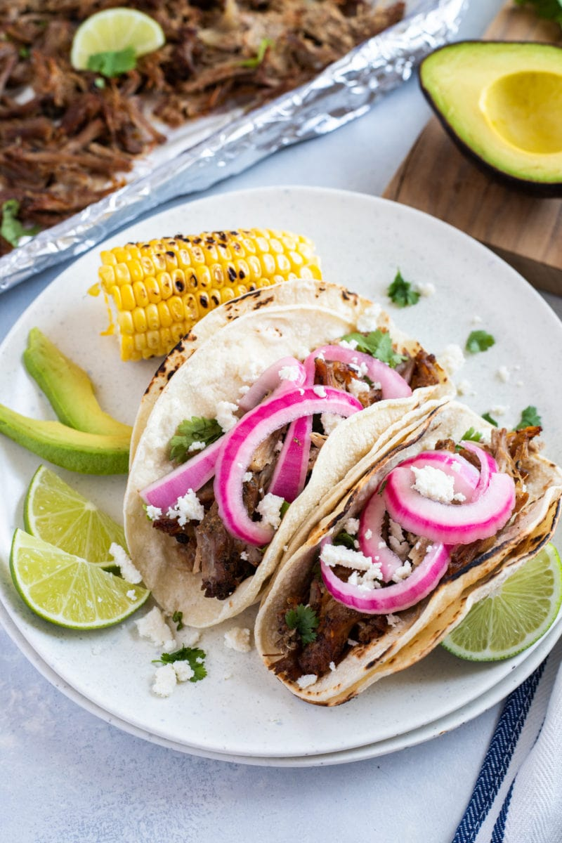 Pork Carnitas tacos topped with pickled onions and lime slices, avocado and corn on the side.