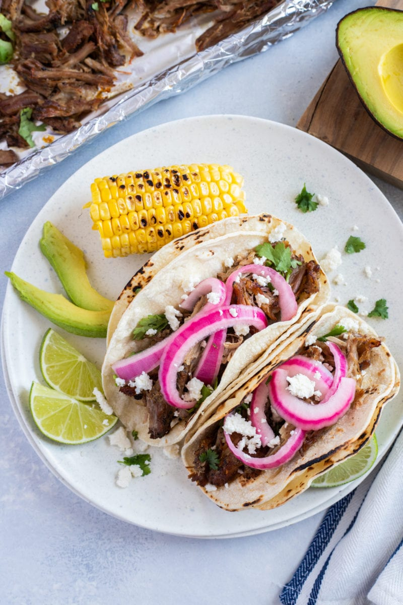 Pork Carnitas tacos topped with pickled onions and queso fresco and served with lime slices, avocado and grilled corn on the side.