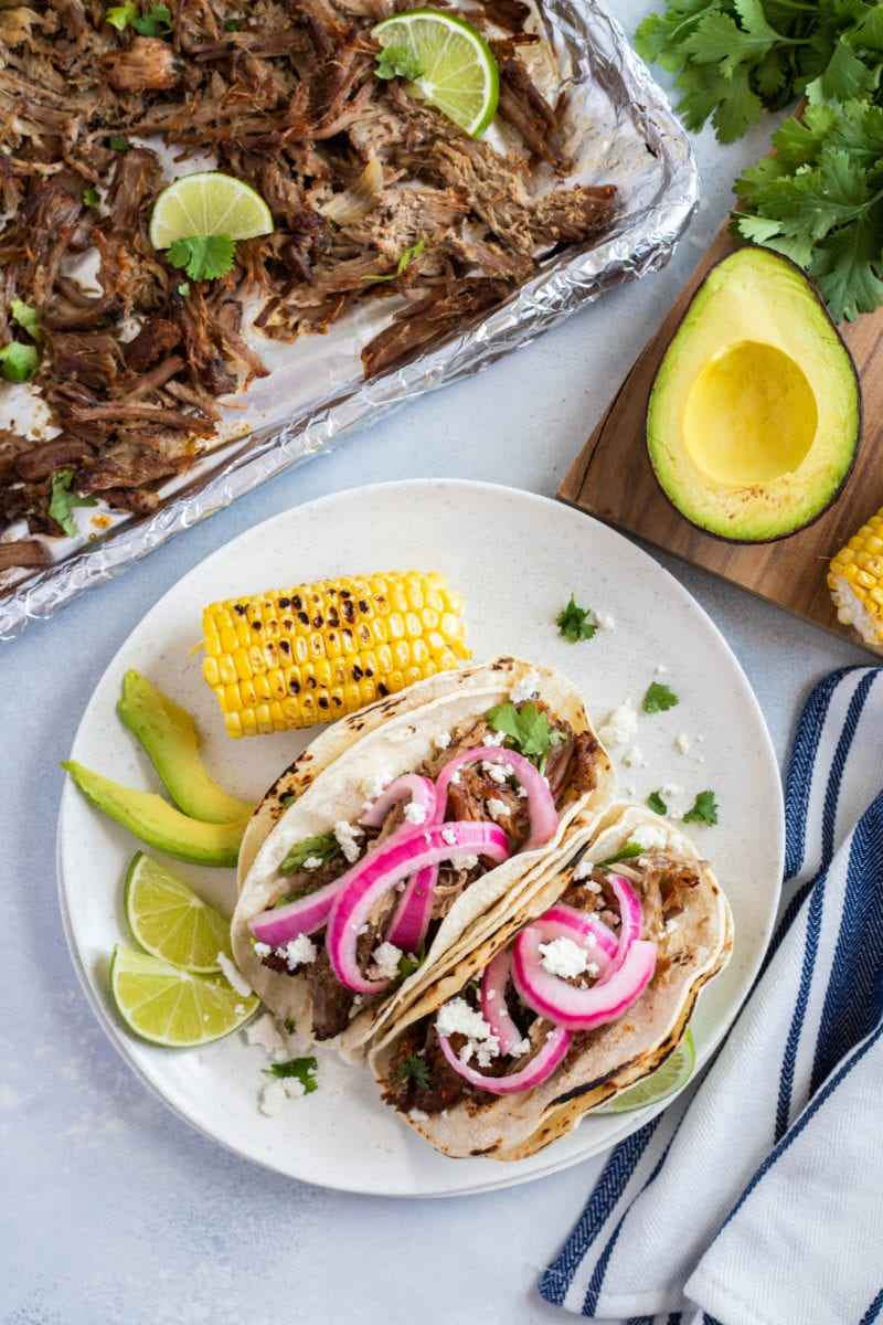 Pork carnitas tacos topped with pickled onions and queso fresco and served with lime slices, avocado and grilled corm on the side.