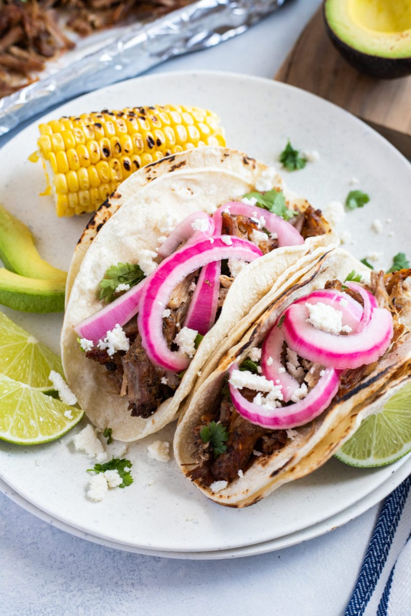 slow cooker carnitas tacos on a white plate