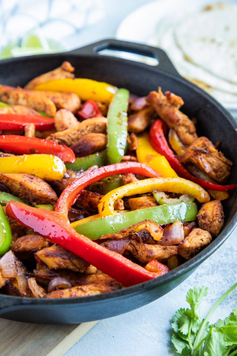Close up of chicken fajitas in skillet.