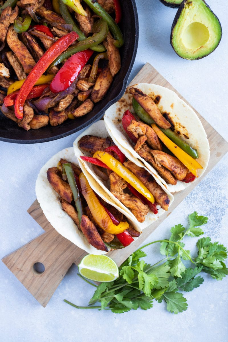 Chicken fajitas piled high onto flour tortillas served with avocado and lime wedges.