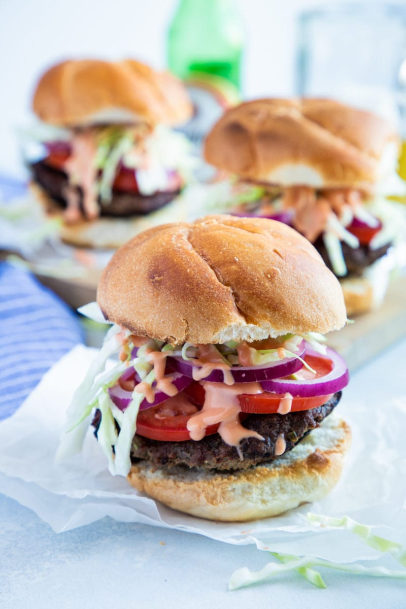 Three Dominican burgers in buns and loaded with toppings.