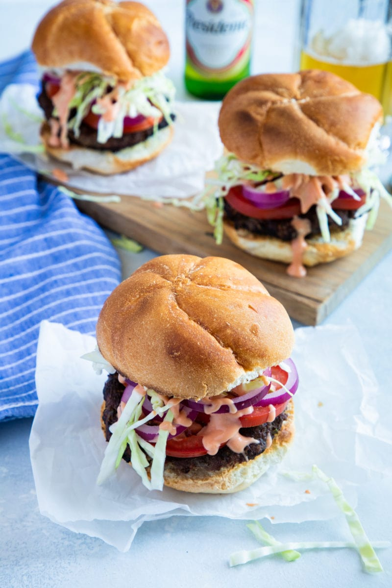 Three Dominican burgers served in buns.