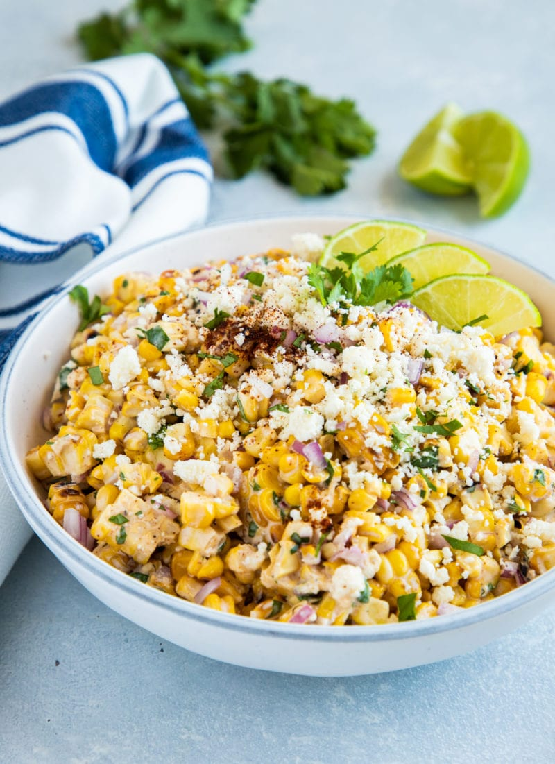 Close up of the Mexican corn salad topped with cotija, lime slices and fresh cilantro.