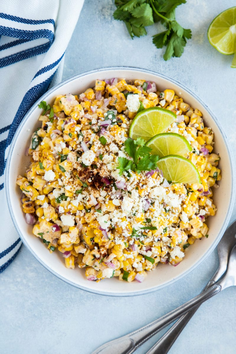 Mexican corn salad in a white bowl garnished with lime and cilantro.
