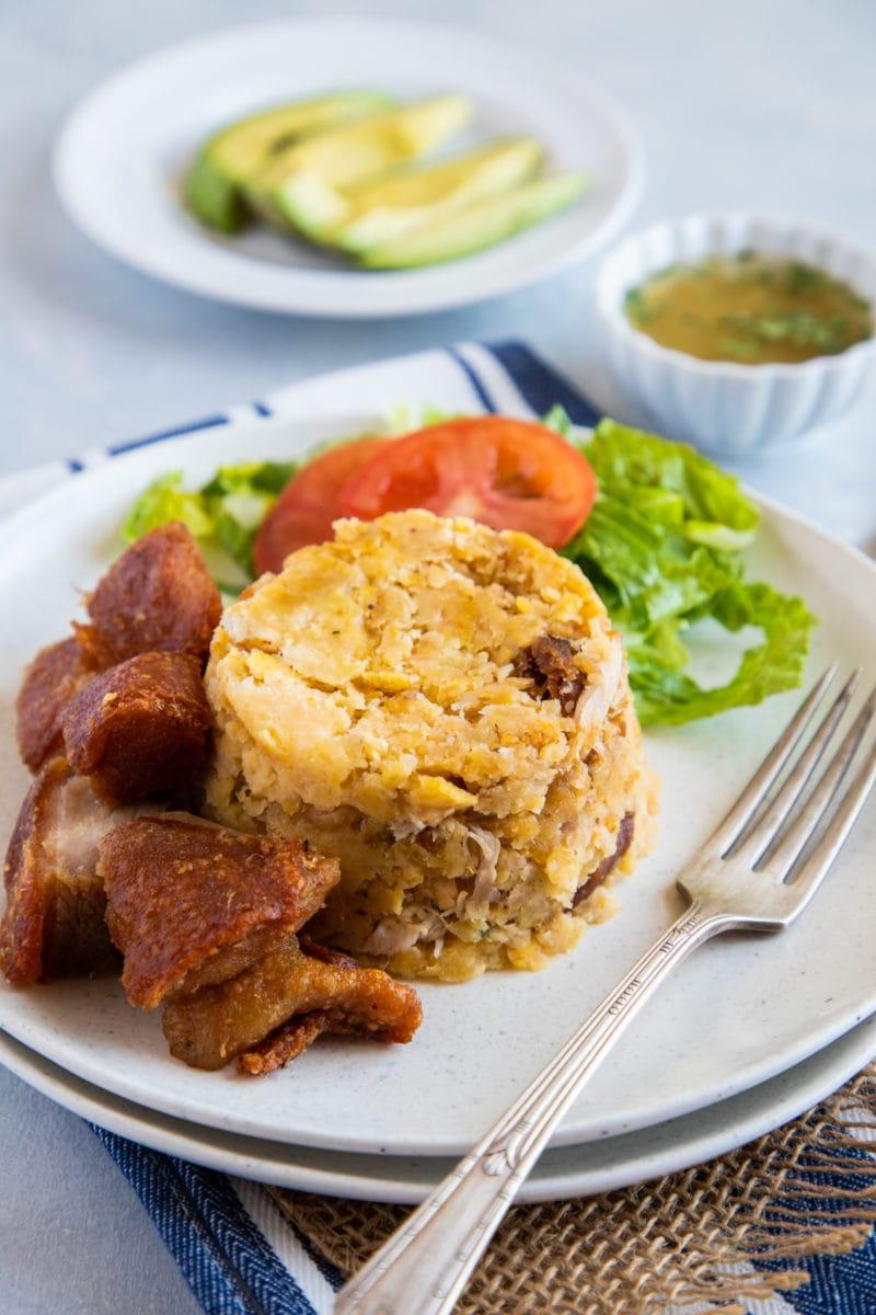 Mofongo tradicional servido en un plato con chicharron, mojo de ajo y aguacate.