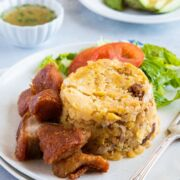 Mofongo served on a plate with a side salad and a fork.