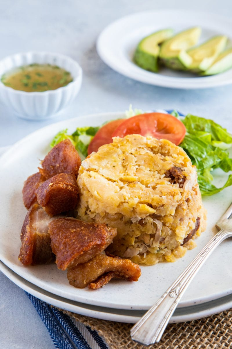 Traditional Mofongo served on a plate with extra chicharron and garlic mojo and avocado on the side.