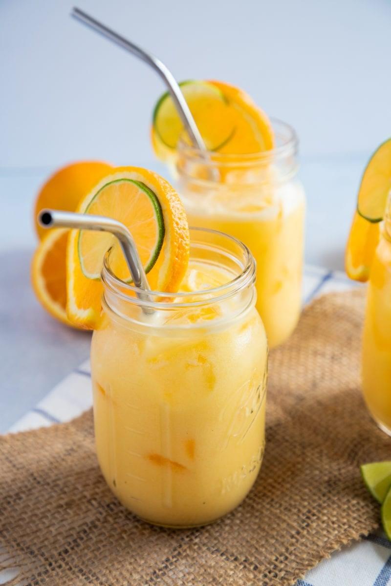 Morir Soñando juice served in mason jars garnished with orange slices and a metal straw.