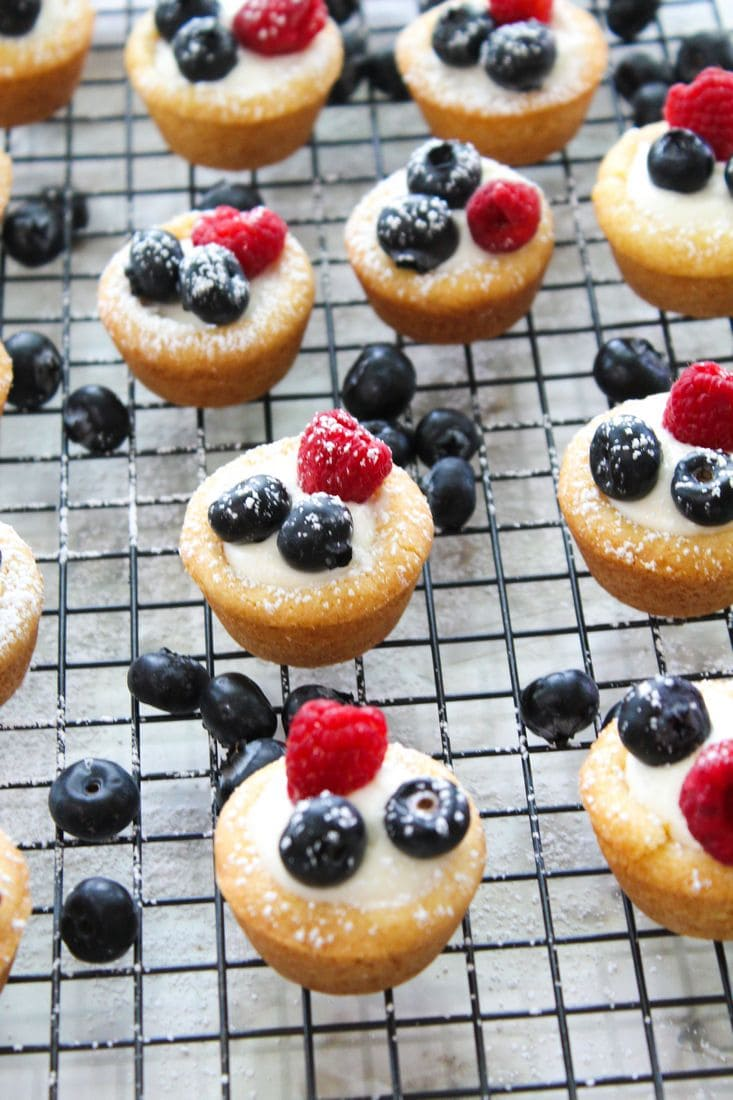 Seven berry cookie cups on a cooling rack.