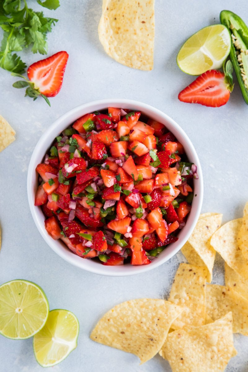 Strawberry Salsa served on a white bowl with corn chips on the side.