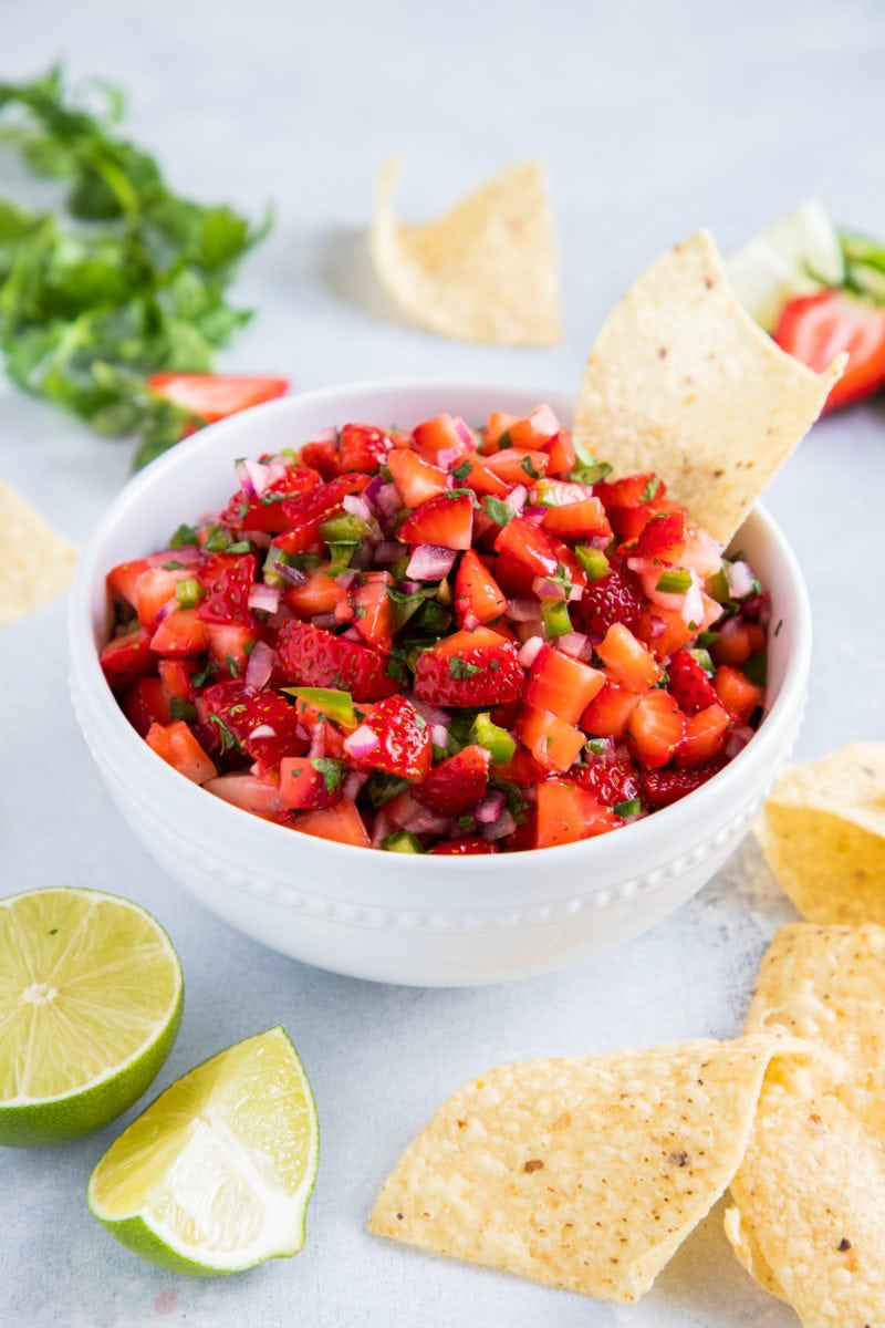 Strawberry Salsa served on a white bowl with corn chips on the side and one single corn chip in the bowl.