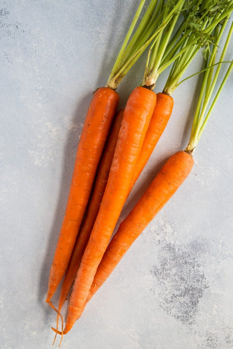 Five carrots on a white surface.