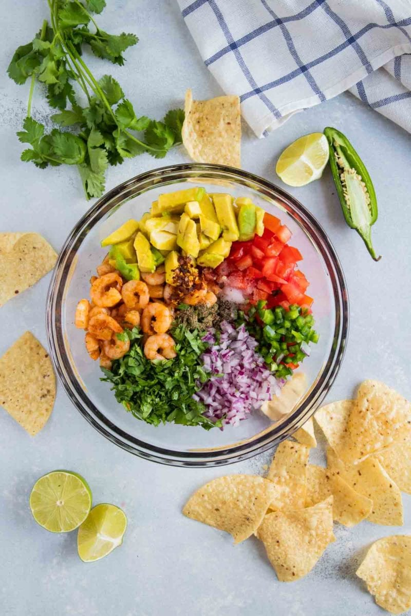 Ingredients for Avocado Shrimp Salsa in a large clear bowl.