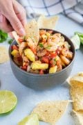 A tortilla chip being dipped into the spicy shrimp salsa.