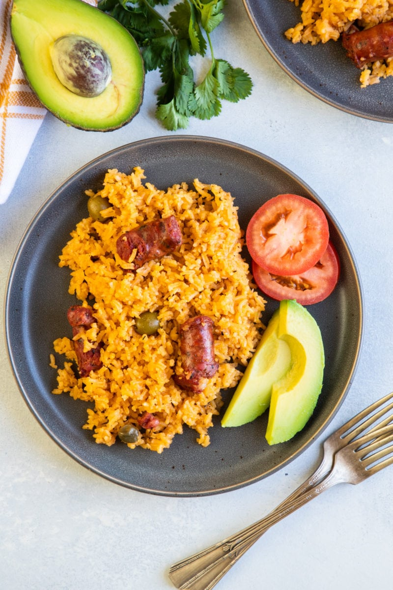 Over head shot of rice with sausage served on a plate with tomato and avocado on the side.