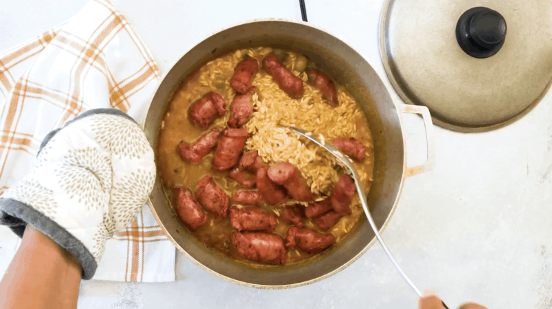 Mixing the sausage with the rice.