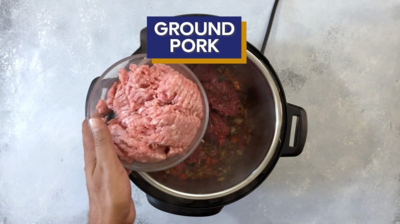 Ground pork being placed into the Instant Pot.