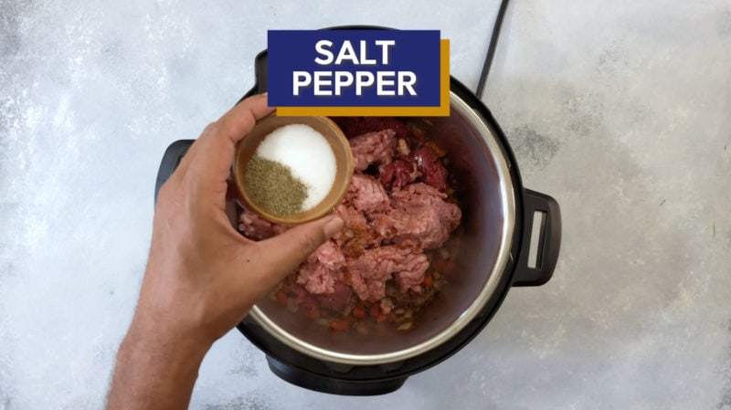 Salt and pepper being added to the pressure cooker.