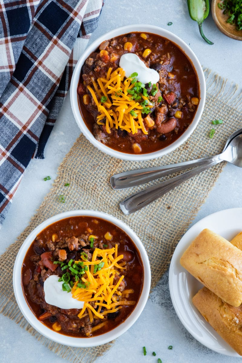Slow Cooker Chili served in two bowls with cornbread on the side