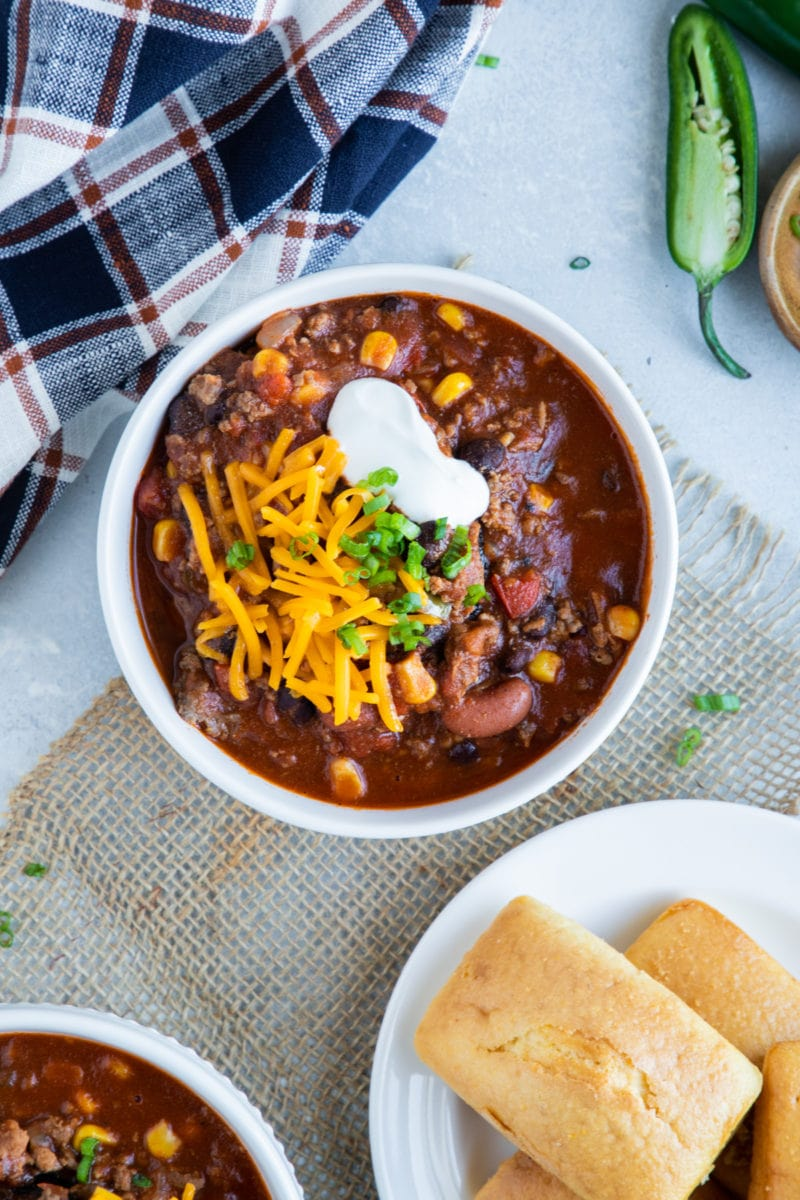 Overhead image of chili served in white bowl with cornbread on the side.