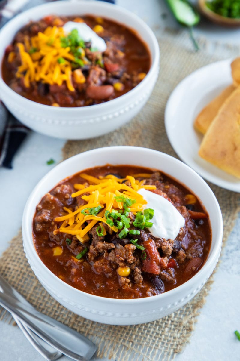 Two bowls of slow cooker chili topped with cheese, sour cream and scallions.