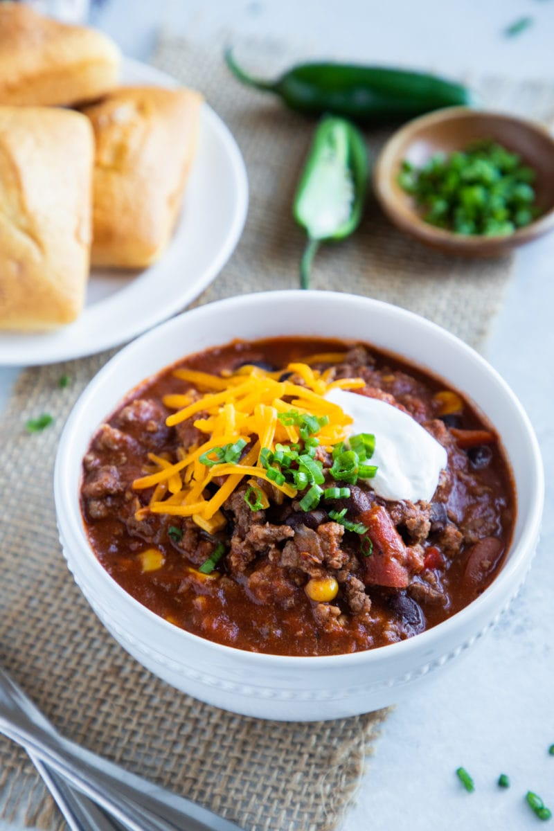 Slow cooker chili served in a white bowl topped with cheese, sour cream and scallions. Cornbread and jalapeño on the side.