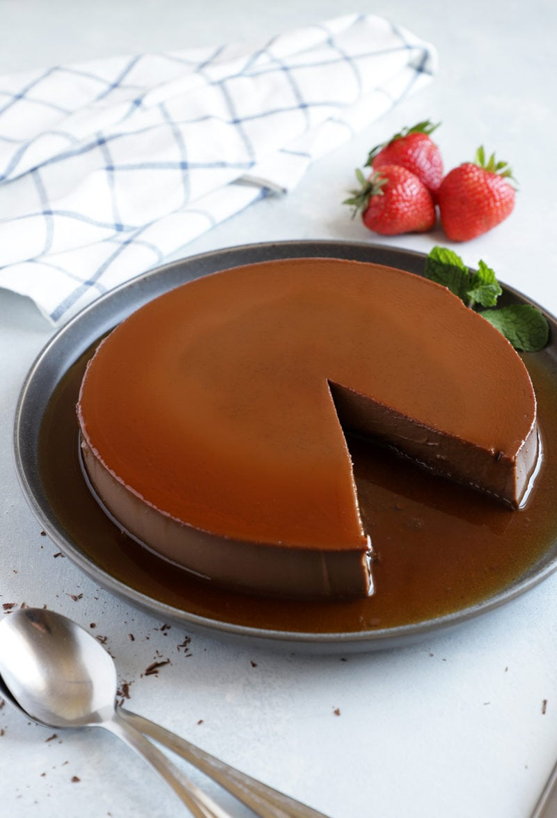 chocolate flan on grey platter with a slice cut out