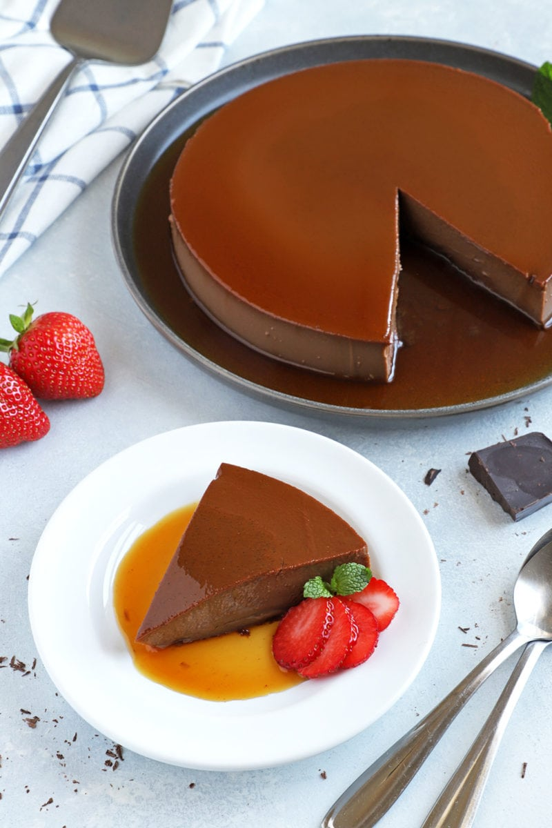 Chocolate flan slice served on a white plate with strawberries on the side.