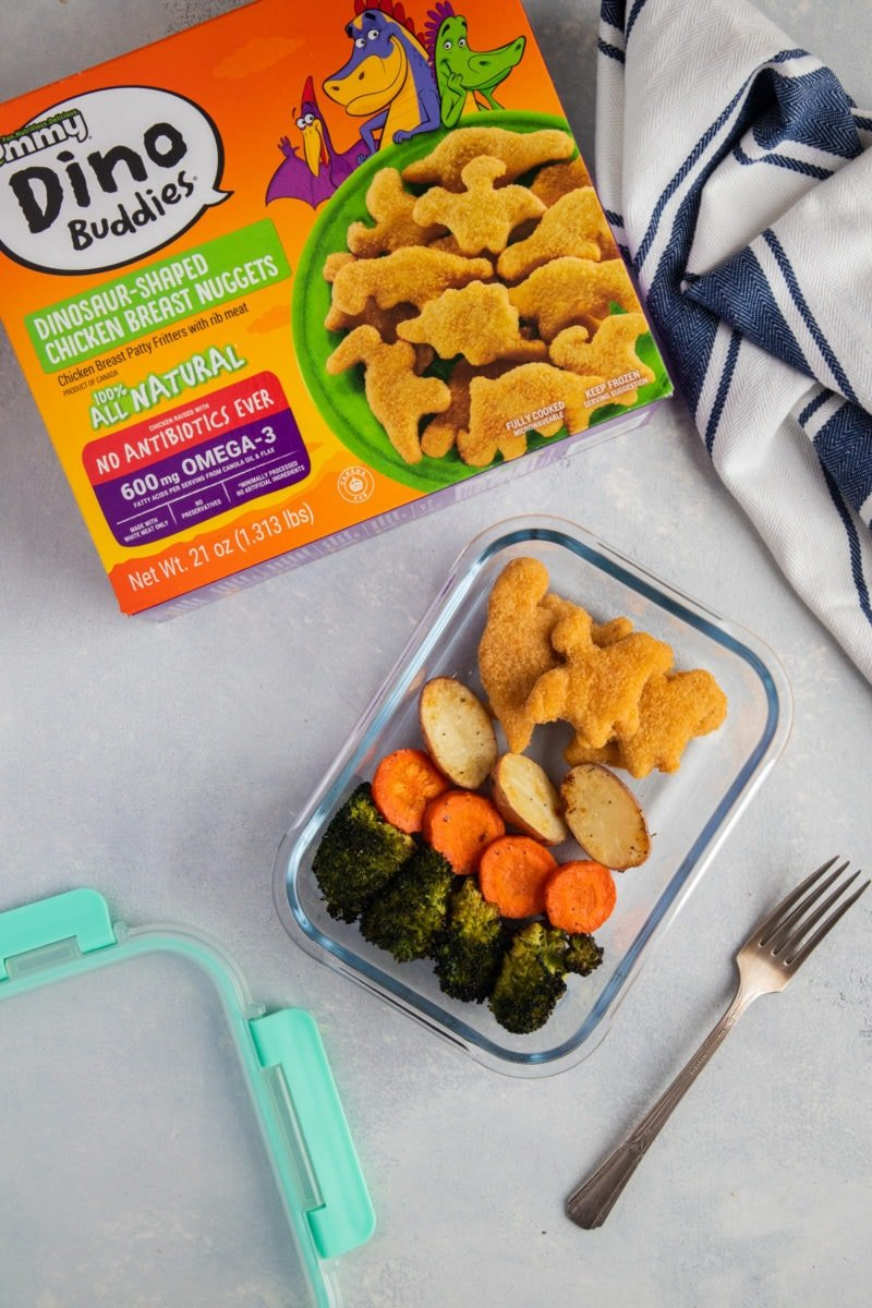 Yummy Dino Buddies with roasted vegetables on a glass food container and box of Dino Buddies on the side